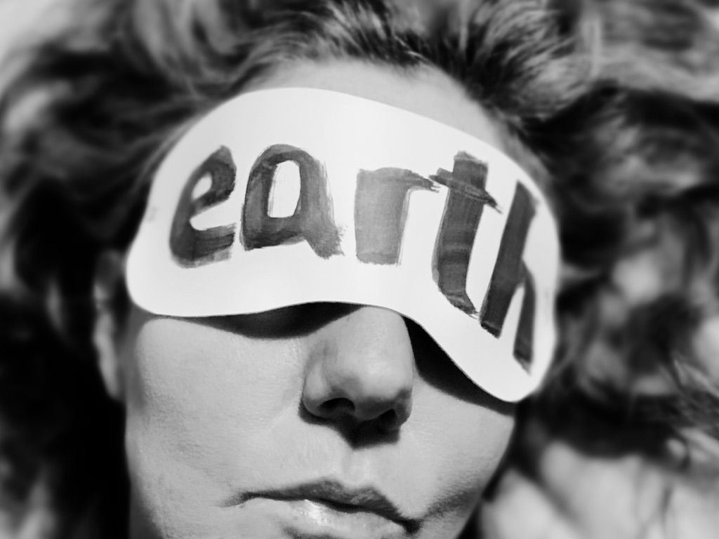 Savitri D of the Stop Shopping Choir wearing Earth mask