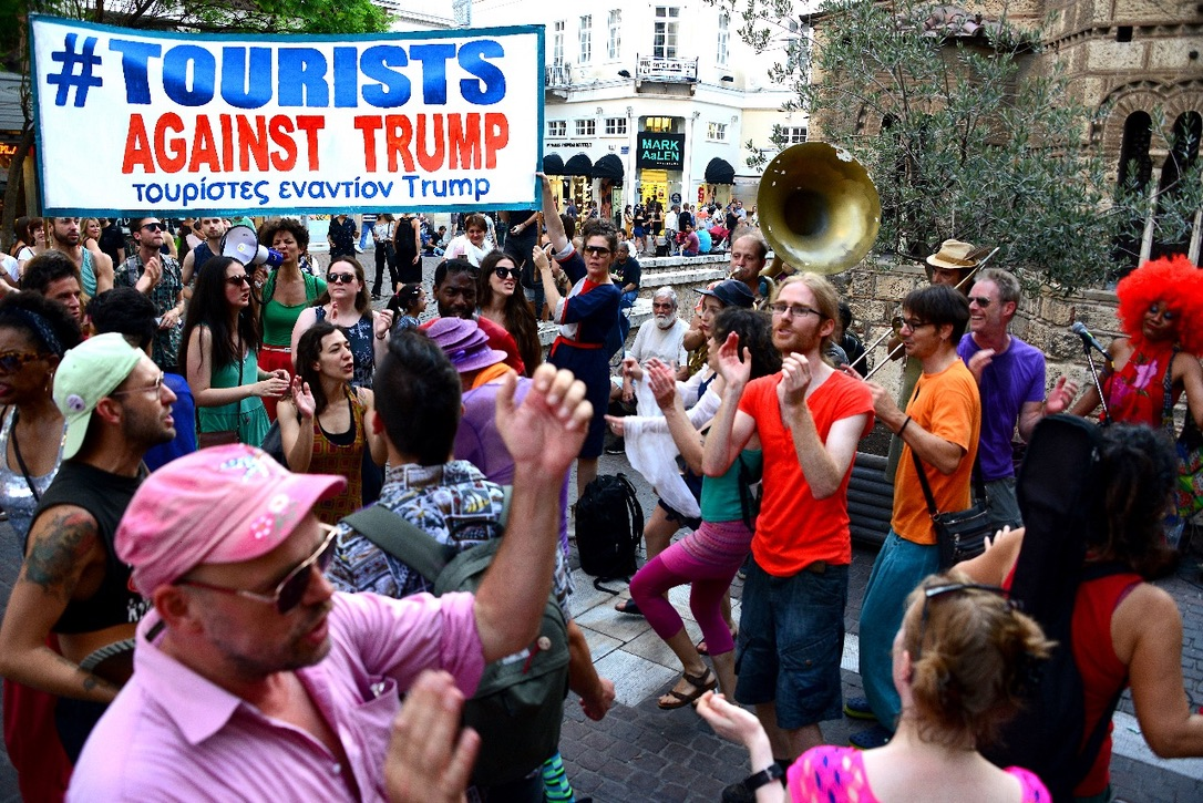 """Stop Shopping Choir holding banner: """"Tourists Against Trump"""""""